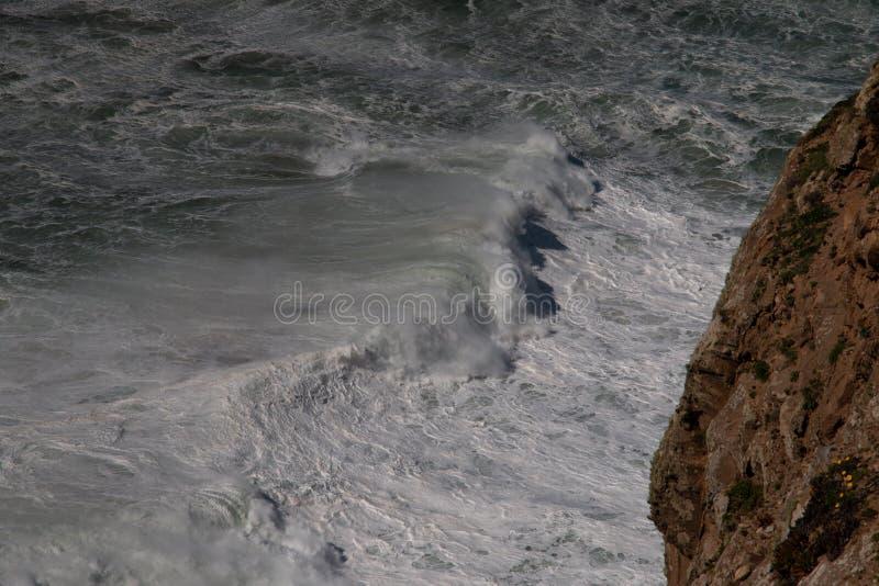 Água incomodada com espuma branca e um penhasco no primeiro plano foto de stock