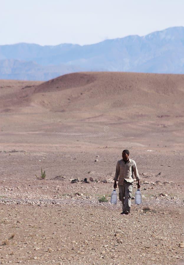 Água levando do homem através do deserto