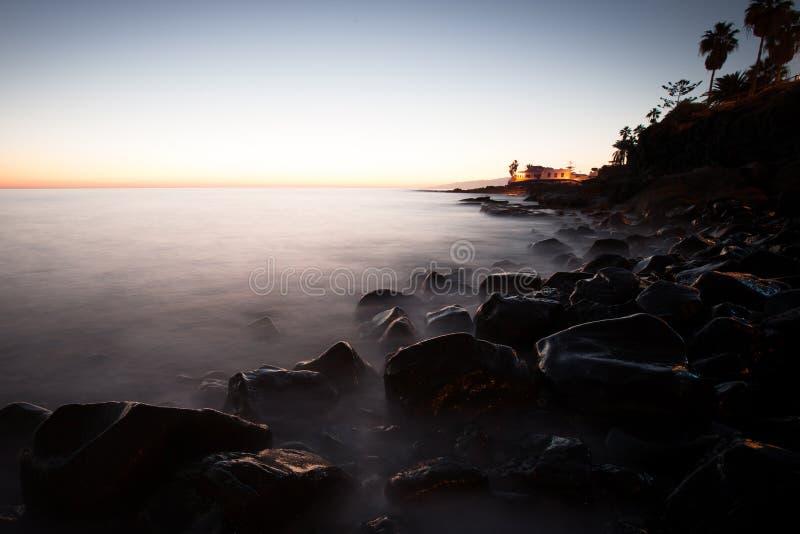 Água místico do oceano em um custo de pedras pretas fotos de stock royalty free