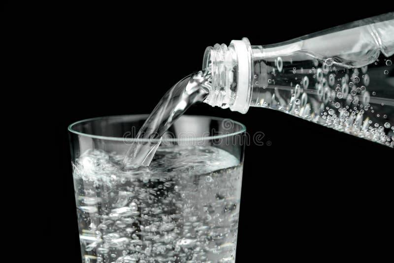 Água mineral de derramamento no vidro fotos de stock