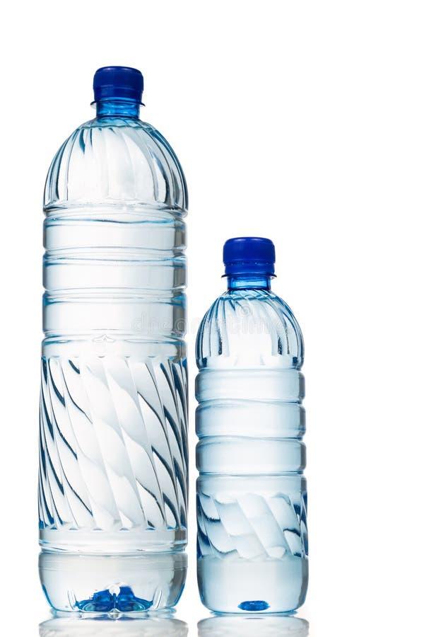Água mineral grande e pequena no fundo plástico do branco da garrafa foto de stock royalty free