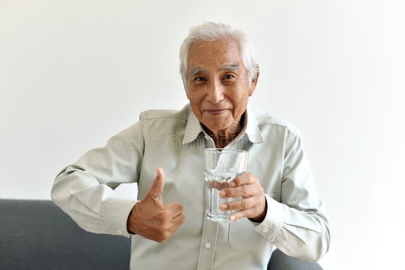 A água potável é bom hábito saudável para o ancião, polegar asiático de sorriso idoso da mostra do homem até o vidro da água refi imagem de stock royalty free