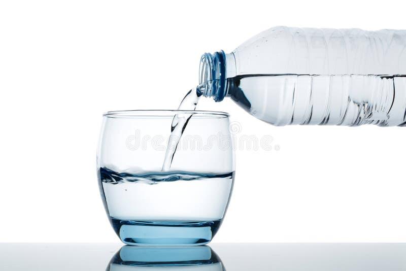 A água potável é derramada no vidro da garrafa imagens de stock royalty free