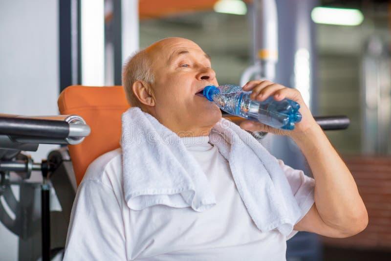 Água potável agradável do homem superior no gym fotografia de stock