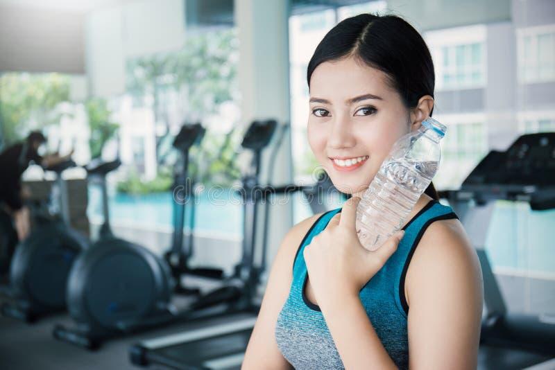 Água potável asiática da jovem mulher após o exercício no clube de esporte imagens de stock royalty free