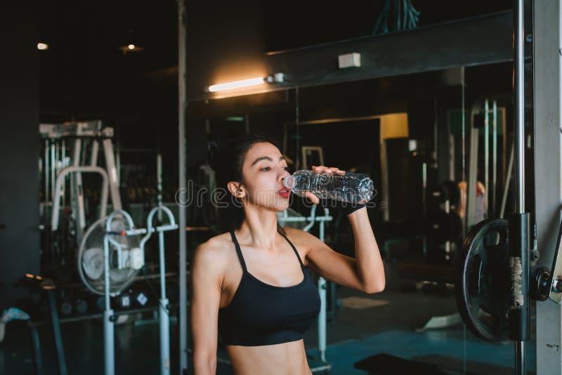 Água potável asiática da jovem mulher no gym imagens de stock
