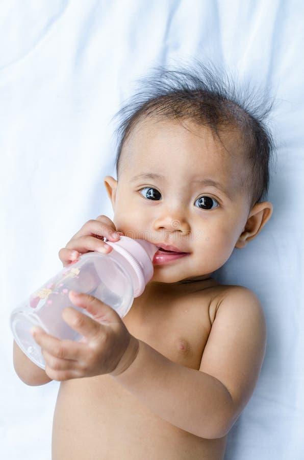 Água potável asiática de sorriso do bebê da garrafa fotografia de stock