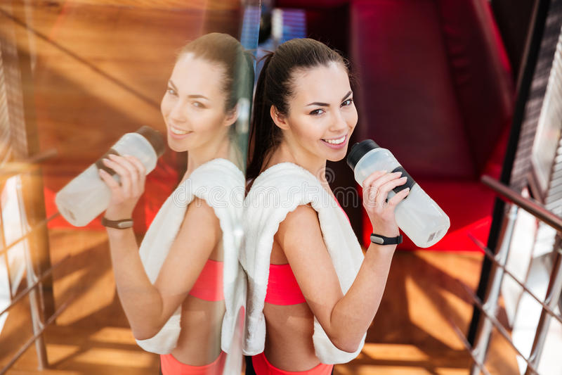Água potável atrativa de sorriso do atleta da mulher no gym imagem de stock
