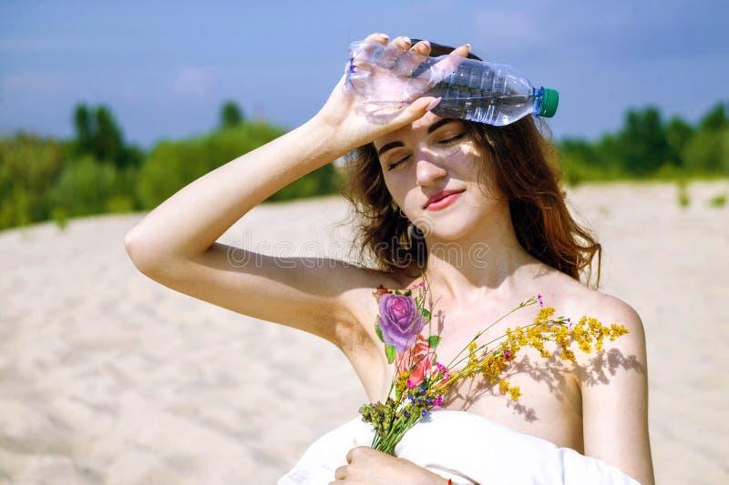 Água potável bonita da mulher da garrafa no deserto imagens de stock