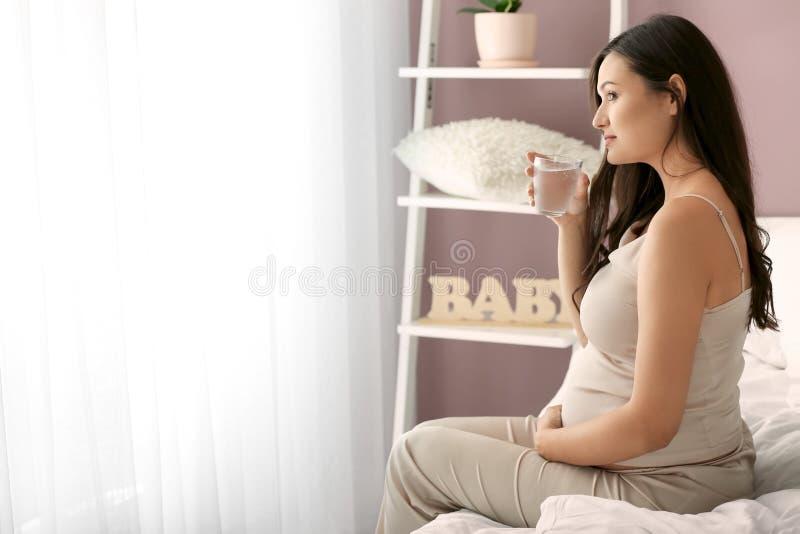Água potável bonita da mulher gravida no quarto fotos de stock