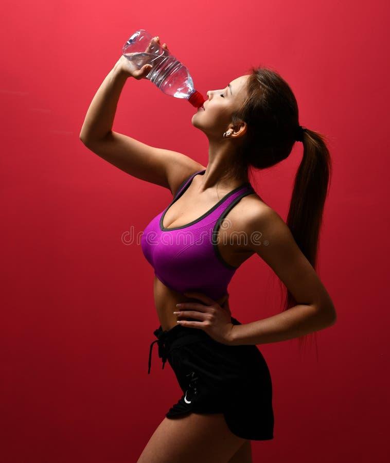 Água potável bonita nova da mulher no sutiã roxo do esporte imagens de stock