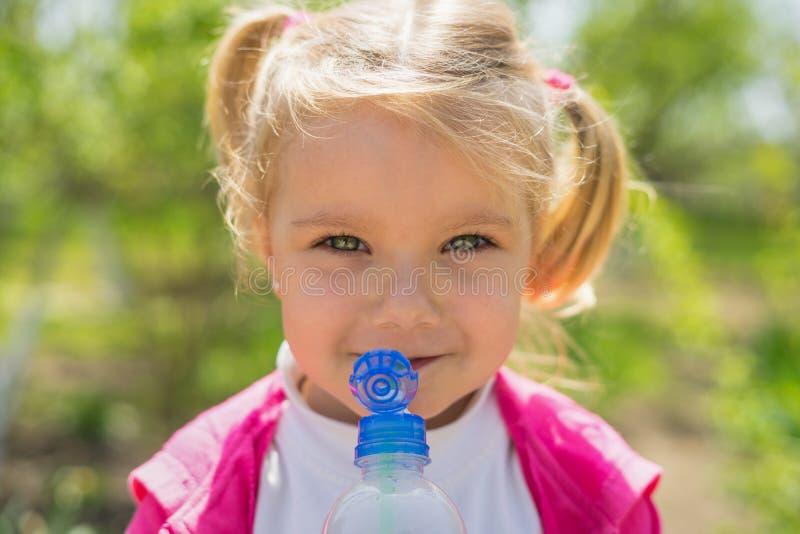 Água potável bonito pequena da menina da garrafa plástica Foto ensolarada fotografia de stock royalty free