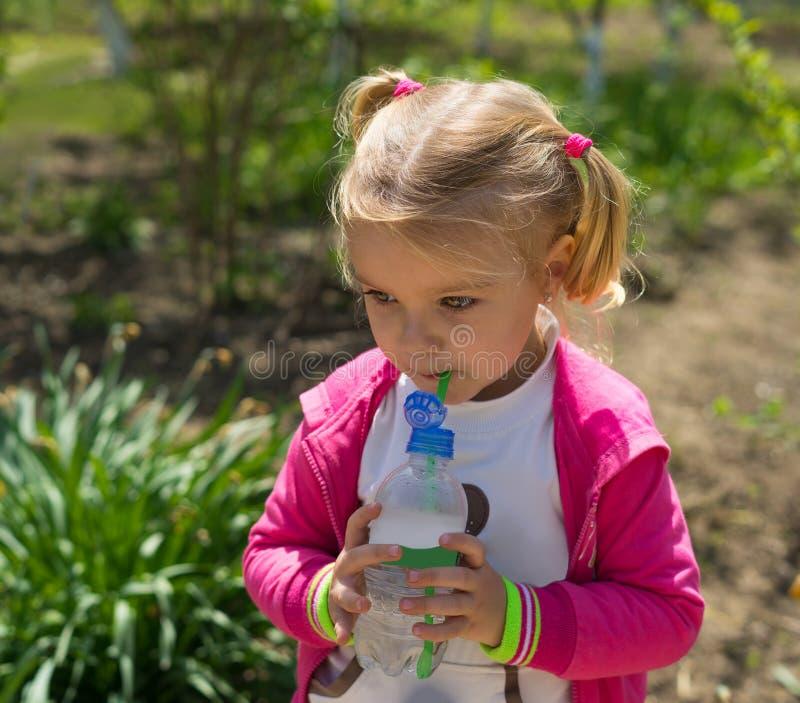 Água potável bonito pequena da menina da garrafa plástica Foto ensolarada imagem de stock