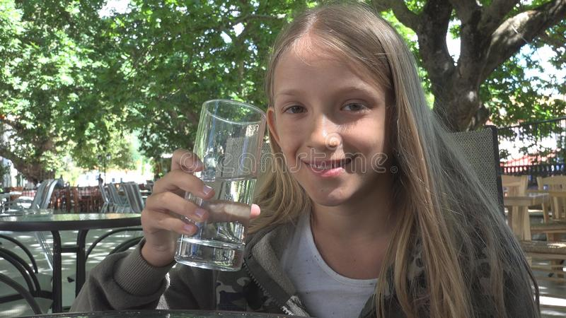 Água potável da criança no restaurante, criança que guarda um vidro da água, sorriso da menina imagens de stock royalty free