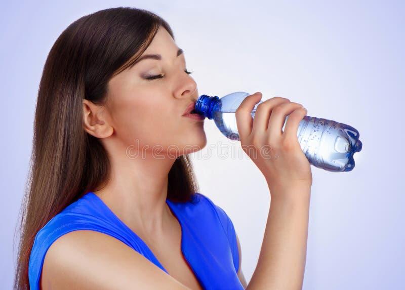 Água potável da jovem mulher da garrafa no fundo azul fotografia de stock