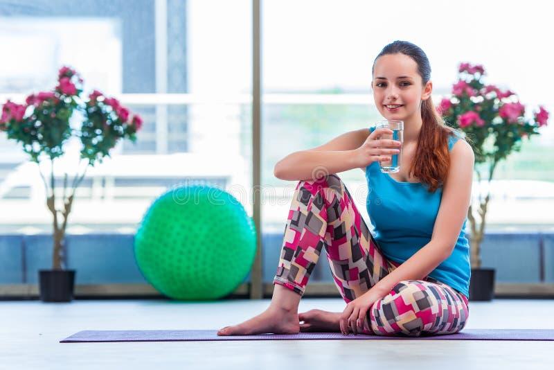 A água potável da jovem mulher no conceito da saúde do gym foto de stock