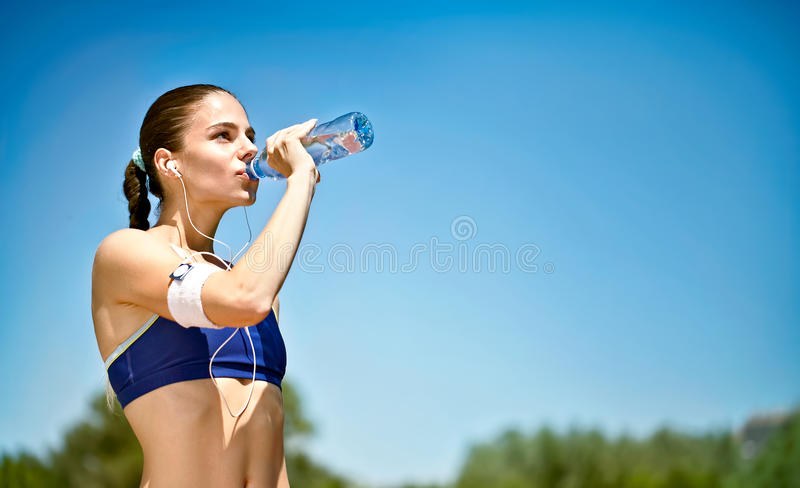 Água potável da mulher após atividades do esporte fotos de stock
