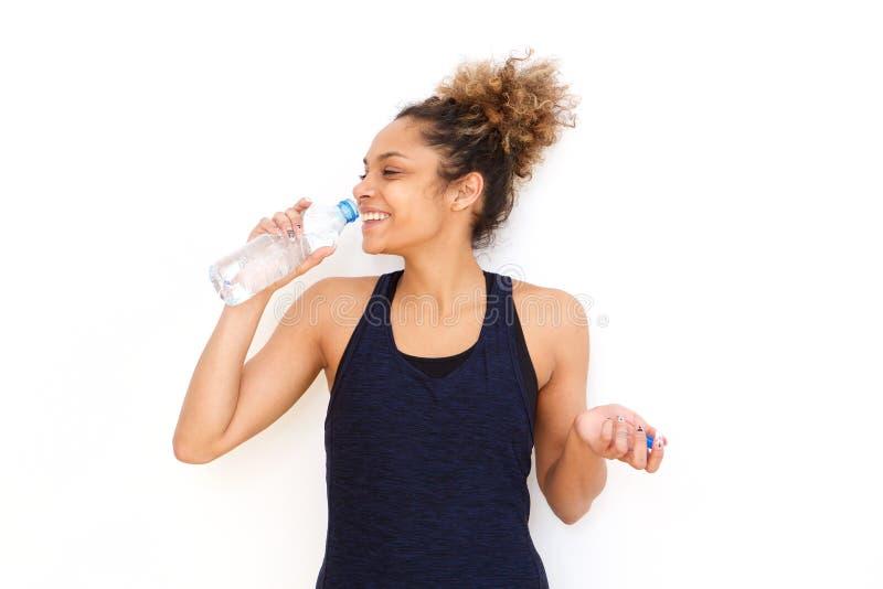 Água potável da mulher da aptidão da garrafa contra o fundo branco foto de stock
