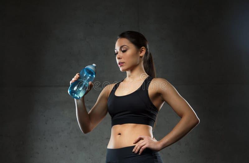 Água potável da mulher da garrafa no gym foto de stock