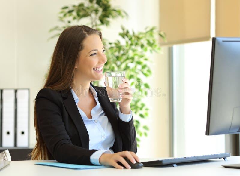 Água potável da mulher de negócios no escritório imagem de stock royalty free