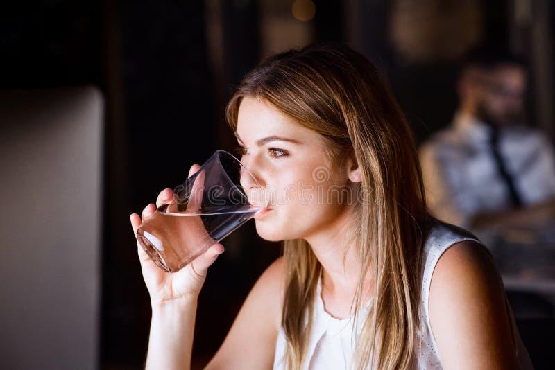 Água potável da mulher de negócios no escritório na noite imagens de stock