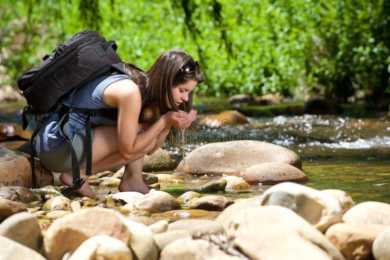 Água potável da mulher do córrego exterior com suas mãos fotos de stock royalty free