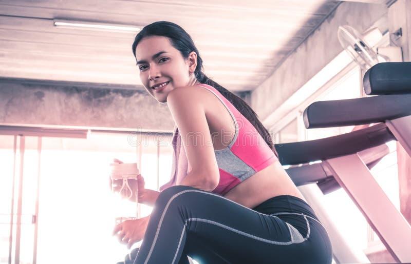 Água potável da mulher no exercício da escada rolante no gym da aptidão foto de stock