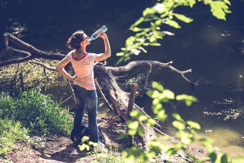 Água potável da mulher pelo lago fotos de stock