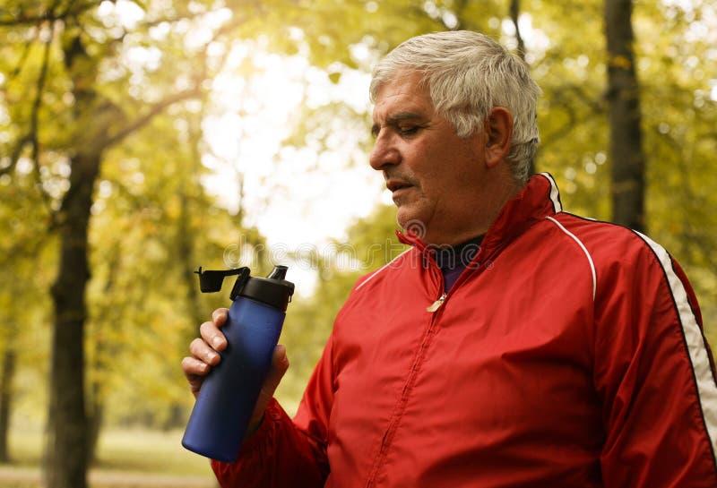 Água potável de meia idade do homem após o exercício imagens de stock royalty free
