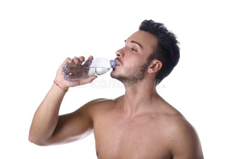 Água potável descamisado considerável do homem novo da garrafa plástica foto de stock royalty free