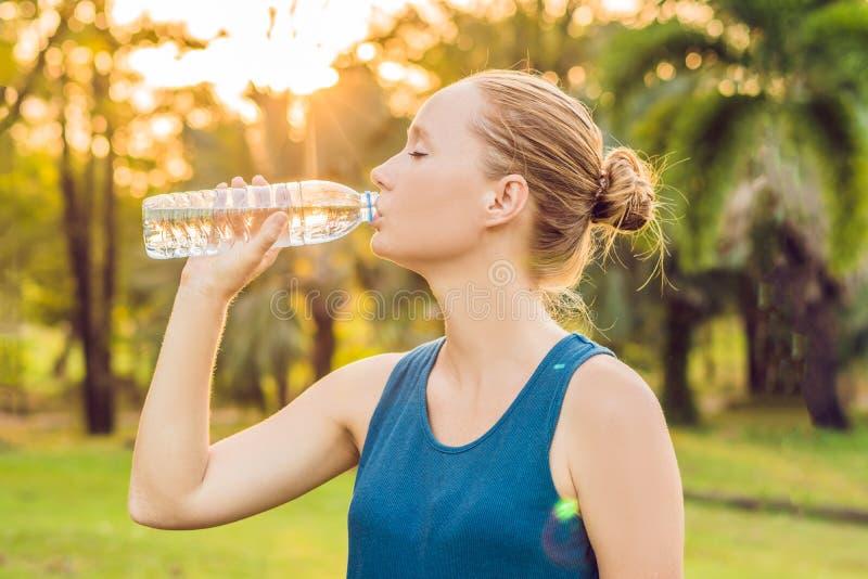 Água potável desportiva atrativa da mulher de uma garrafa após movimentar-se ou correr imagens de stock royalty free