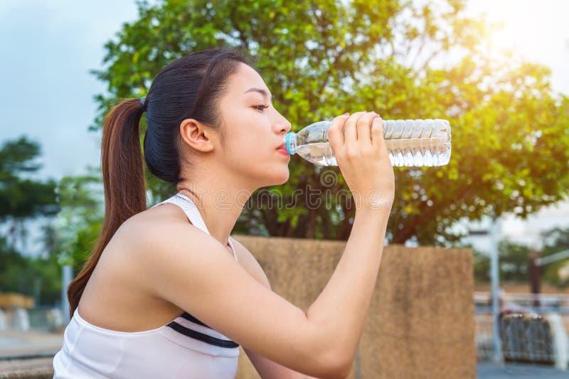 Água potável desportiva da jovem mulher após movimentar-se fotos de stock