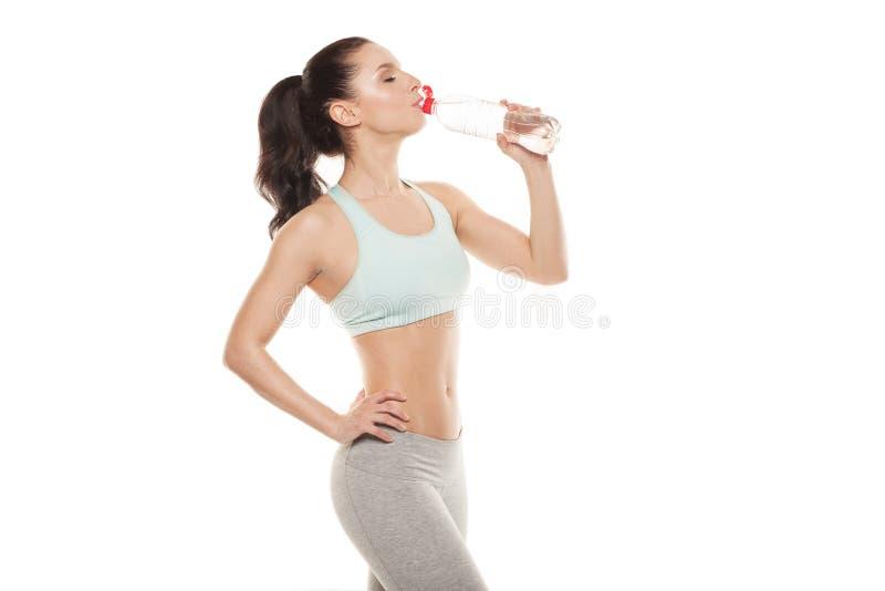 Água potável desportiva da menina de uma garrafa depois que um exercício, treinamento da aptidão, isolou o fundo branco imagens de stock royalty free