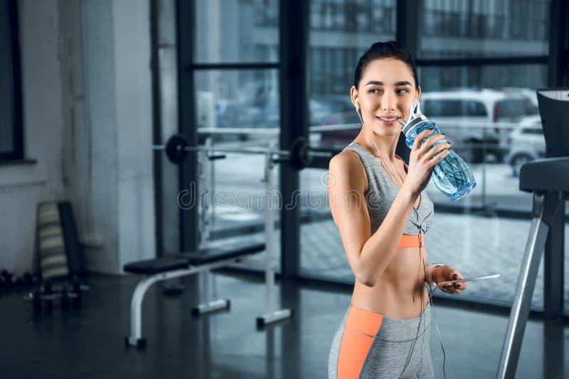 água potável desportiva nova da mulher e vista para trás fotografia de stock