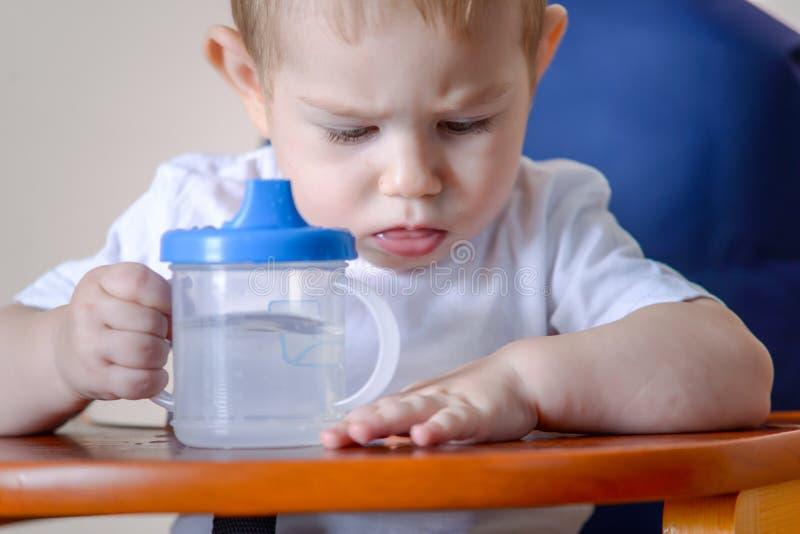 Água potável do bebê que estuda uma garrafa plástica ao sentar-se em uma cadeira na cozinha foto de stock royalty free
