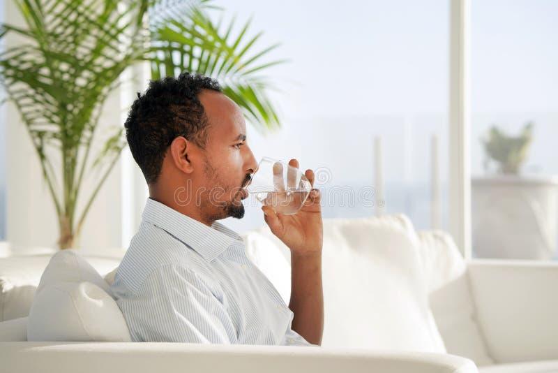 Água potável do homem do Afro em um vidro fotos de stock