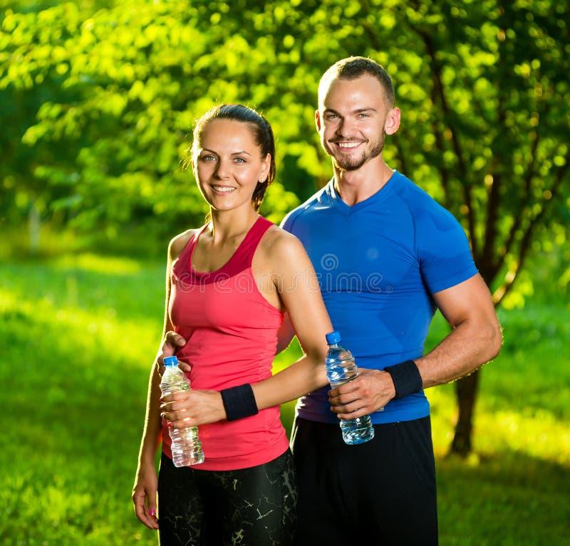 A água potável do homem e da mulher da garrafa após a aptidão ostenta o exercício fotografia de stock royalty free