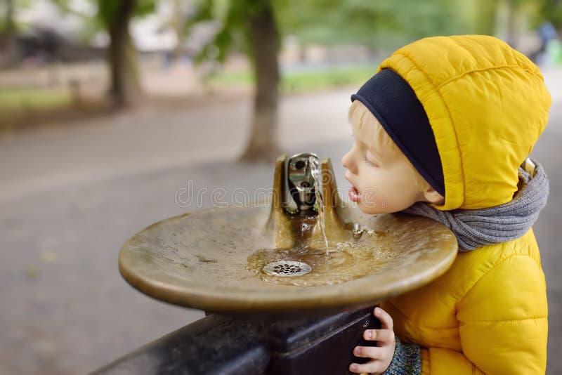 Água potável do rapaz pequeno da fonte da cidade durante o passeio no Central Park, Manhattan, New York, EUA fotos de stock