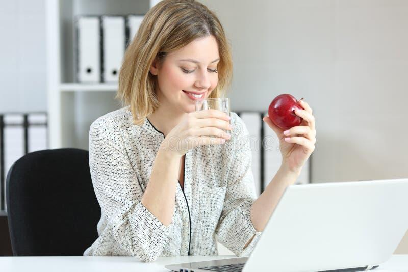 Água potável do trabalhador de escritório e comer uma maçã imagens de stock
