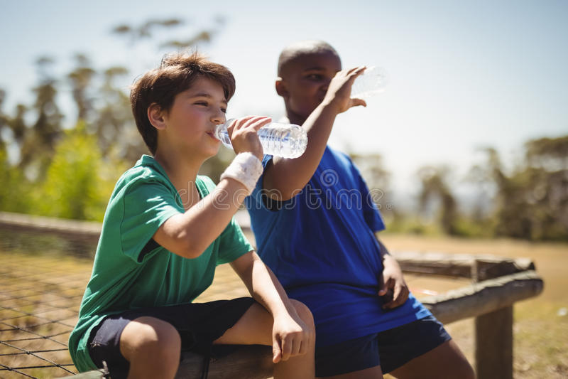 Água potável dos meninos após o exercício durante o curso de obstáculo fotografia de stock royalty free