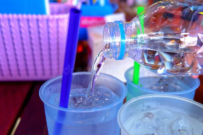 A água potável está sendo derramada em um copo plástico foto de stock