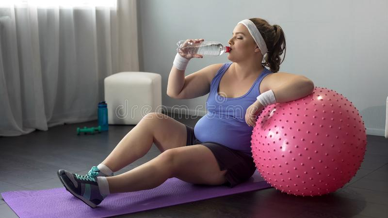 Água potável excesso de peso da senhora após o exercício, deleitado com perda de peso, alegria fotos de stock