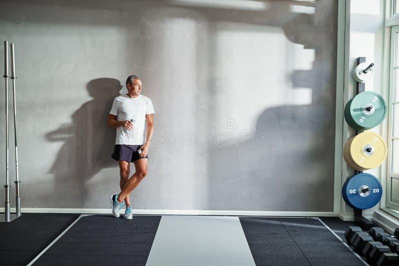 Água potável madura do homem em seguida em uma sala de peso do gym imagem de stock