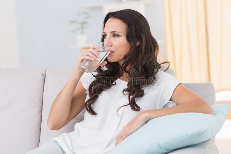 Água potável moreno bonita no sofá imagem de stock
