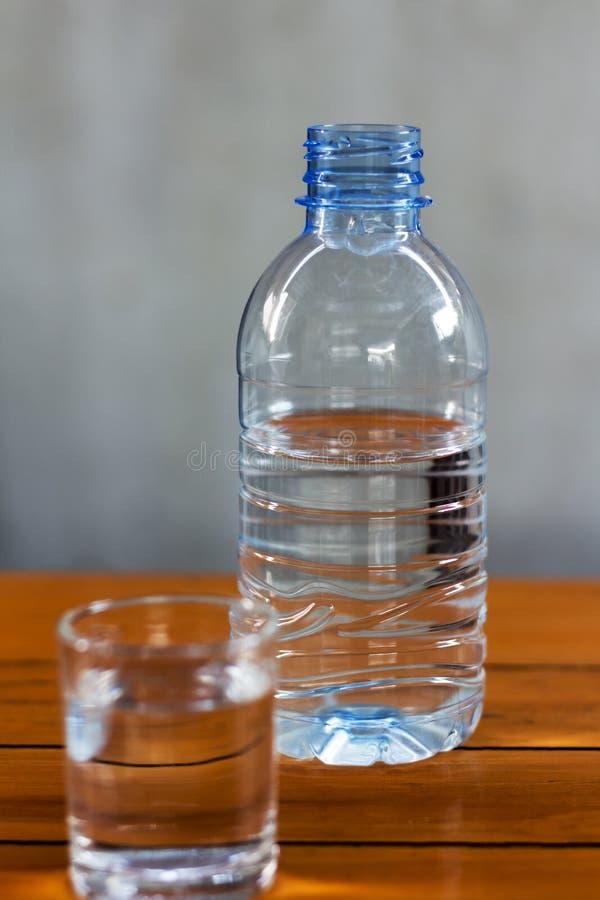 Água potável nas garrafas de vidro e plásticas em uma tabela de madeira fotografia de stock