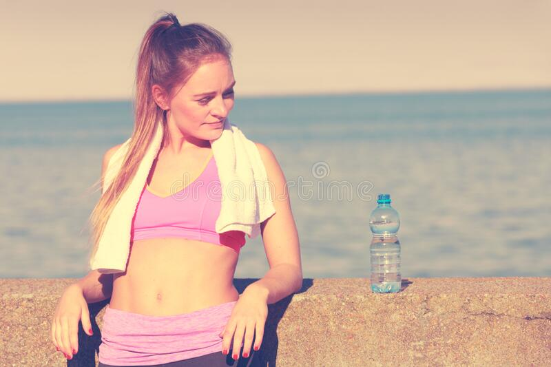 Água potável para mulheres após ginástica desportiva ao ar livre imagem de stock royalty free