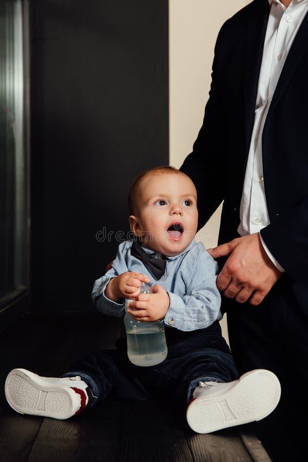 Água potável pequena do bebê da garrafa Vestido à moda fashionably, foto de stock royalty free