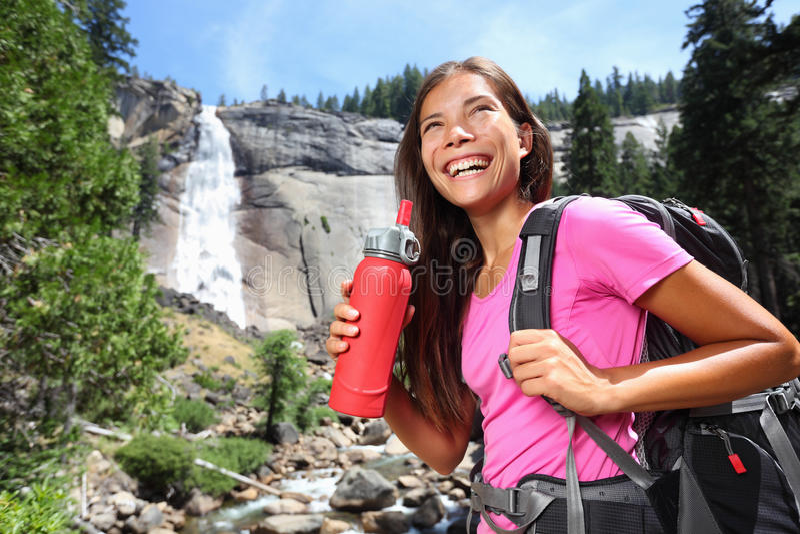 Água potável saudável da menina do caminhante na caminhada de natureza foto de stock royalty free