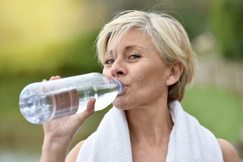 Água potável superior bonita da mulher após excercising fotografia de stock
