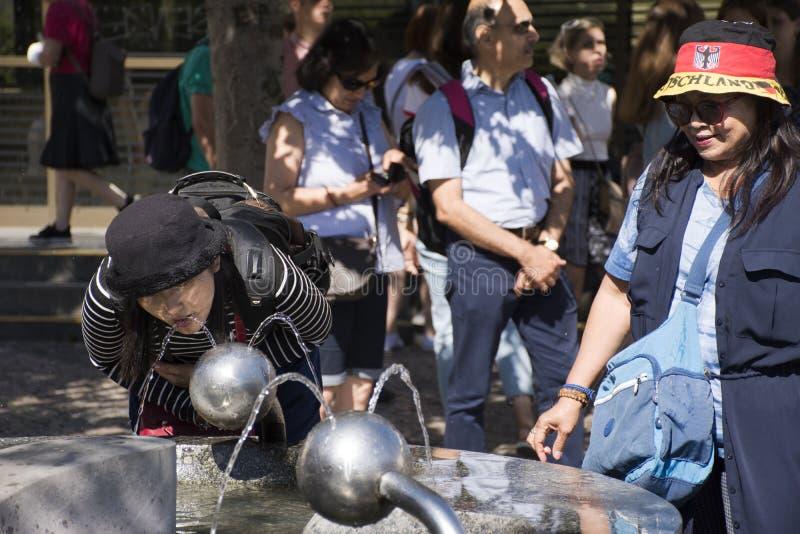Água potável tailandesa asiática da mulher da água potável pública no quadrado do jardim imagens de stock royalty free